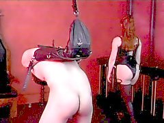 Leather wearing dominatrix spanks guys ass