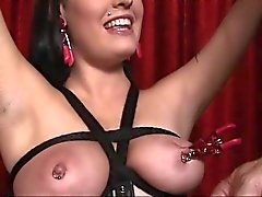 Slut in leather loves being restrained and having her nipples clamped