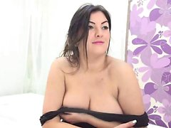 Busty brunette removes her black dress to show her big tits