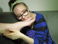Brunette wearing glasses licking big feet