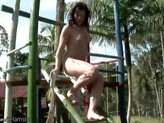 Brunette sheslut is stroking her big cock in public park