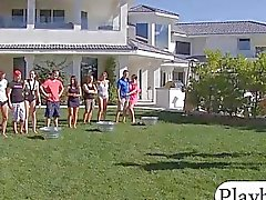 Group of swinging couples playing with water guns outdoors