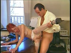 Redheaded older secretary sucks boss's cock at her desk