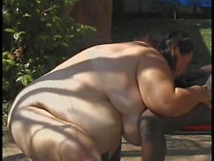 Obese brunette sucks prone black dude's big cock outdoors