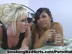 Two teens smoke glass pipe on bed.