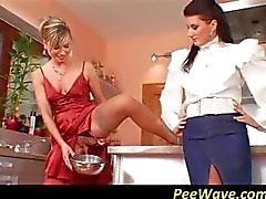Two horny sluts share a cock in the kitchen and take turns sucking