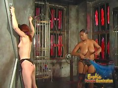 Skinny redhead slut has some dungeon fun with an ebony hussy