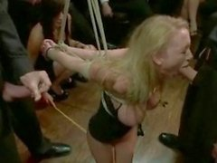 Awesome busty blonde tied suspended in the air in front ofpeople