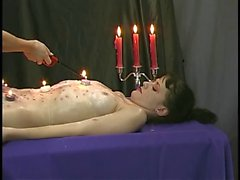 Slim brunette lies prone while hot candle wax is dripped all over her body