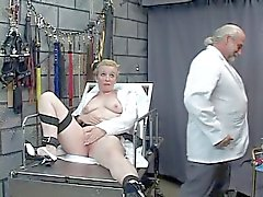 Mad scientist pours hot wax on bound thick mature blonde's clit in dungeon