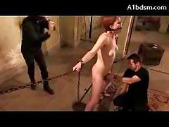 Girl On Chains Clips On Her Pussy Vibrator Under Mouthgag Getting Whipped By 2 Guys In The Basement