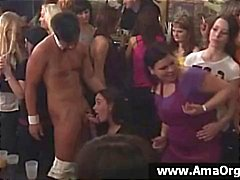 Party girls at a very large party take turns sucking strippers cock
