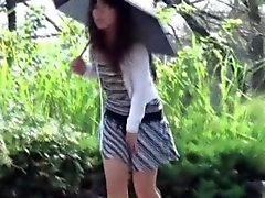 Asian chick pees outdoors in rain